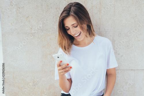 canvas print picture junge frau lacht und schaut auf ihr smartphone