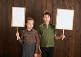 Children are dressed in retro military uniforms. They're holding blank posters for veterans portraits. - 209657102