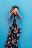 lachende frau mit einem langen sommerkleid steht vor einer blauen wand - 209657156
