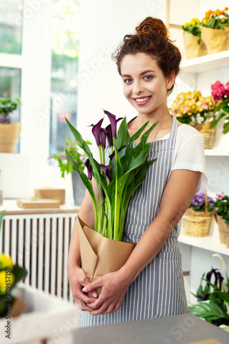 Foto Murales Favourite hobby. Joyful positive woman enjoying plants while standing in the flower shop