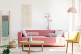 Yellow chair next to pink sofa and wooden table in pastel living room interior with flowers. Real photo - 209657326