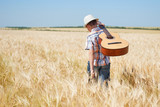 child boy with guitar is in the yellow wheat field, bright sun, summer landscape - 209657381