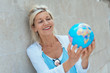 glückliche ältere frau hält einen globus in der hand und plant eine reise