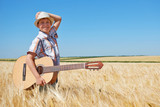 child boy with guitar is in the yellow wheat field, bright sun, summer landscape - 209657514
