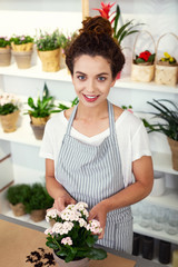 My occupation. Cheerful professional florist looking at you while holding a flower