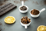 Cloves, coffee and cinnamon set on a table next to a bar chocolate and orange slices