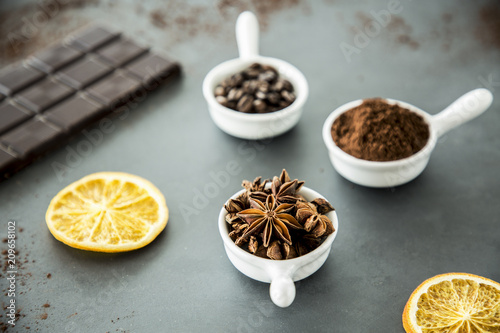Cloves, coffee and cinnamon set on a table next to a bar chocolate and orange slices - 209658102