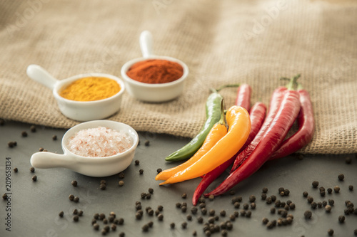 Chili peppers, salt, turmeric powder and red pepper powder on a table with black pepper strewn around