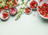 Homemade tasty strawberries jam in glass jar with summer flowers and fresh berries, bowls and spoon on table background, top view. Berries preserve concept, border - 209660194