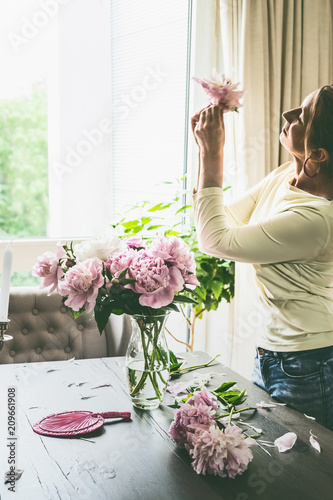 Pretty woman with pink flowers peonies on table in living room, making bouquet in a glass vase at window. Summer still life. Cozy home scene