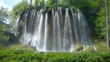 Wide angle view of a beautiful waterfall showering down into a lake in Plitvice Lakes National Park - 209664919
