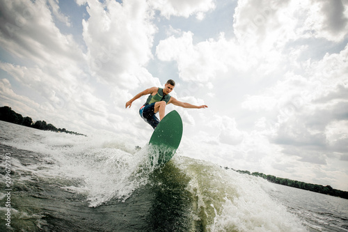 Leinwanddruck Bild Young attractive man riding on the green wakeboard