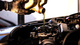 Mechanic fills up the car engine with engine oil - 209683195