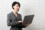business woman with laptop, dressed in a gray suit poses in front of a white wall - 209686144