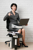 business woman with laptop and folders, dressed in a gray suit poses in front of a white wall - 209686328