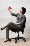 the business woman plays with paper boats, dressed in a gray suit poses in front of a white wall - 209687917