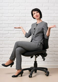 the business woman sitting on a chair, dressed in a gray suit poses in front of a white wall - 209690945