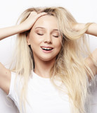lifestyle and people concept - happy blond girl touches her hair. Casual clothes. White background.Close up.