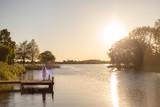 Ein Mädchen tanzt auf einem Bootssteg an einem See im Sonnenuntergang - 209694181