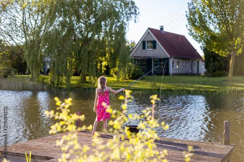 Fototapeta Ein Mädchen steht mit einer Angelrute auf einem Holzsteg an einem See
