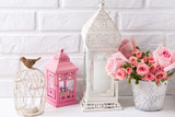 Pink roses  and decorative pink and white lanterns against  white brick wall. - 209707309