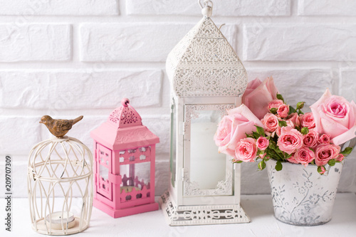 Pink roses  and decorative pink and white lanterns against  white brick wall.