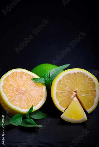 Foto Murales Ripe and juicy lime and lemon with a sprig of mint on a dark table