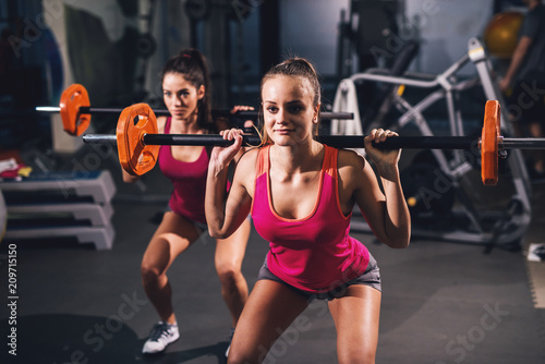 Fototapeta Two young hot girls are doing situps with orange weights on their shoulders in a dark gym.