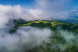 Aerial view over the clouds and mountain peaks