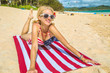 Smiling vintage 50s style woman, laying on american flag beach towel in Hawaiian tropical Lanikai Beach, with American flag bikini in Oahu island of Hawaii, USA. Freedom and 4th July patriotic concept