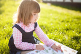 Moscow, Russia. 9 May, 2018. Adorable little girl reading botany book. - 209717913