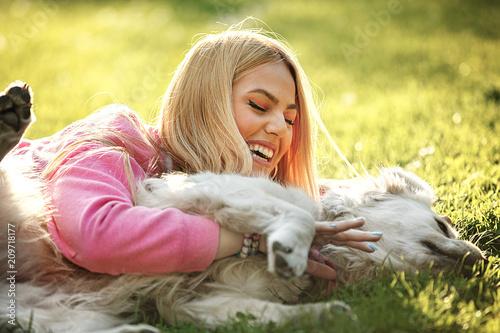 Leinwanddruck Bild Woman enjoying park with dog