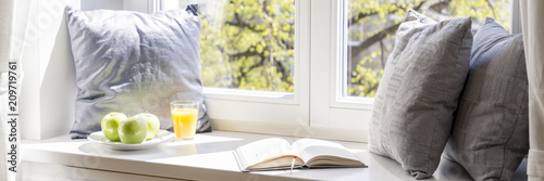 Real photo of windowsill with three grey pillows, open book, green apples on plate and orange juice in glass