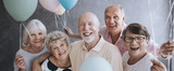 A group of happy, senior friends holding colorful balloons while posing at a party and celebrating birthday together. - 209719922