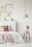 Pink, old-fashioned phone on a wooden side table and a pendant lamp in a serene bedroom interior with white walls - 209720552