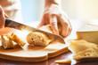 Leinwanddruck Bild - person cutting bread