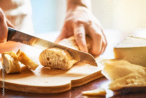 Leinwanddruck Bild person cutting bread