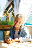 Happy cute girl is sitting in an outdoor cafe. Happy moments - 209731791