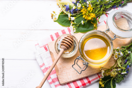 Honey  in a jar with wild herbs on white - 209743561