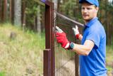 worker installing welded metal mesh fence - 209747720