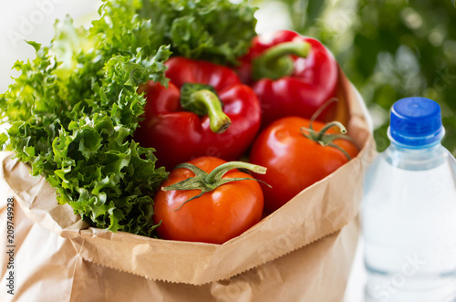 Foto Murales food, diet and healthy eating concept - close up of paper bag with fresh vegetables and water bottle over green natural background