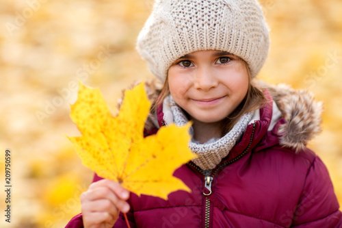 childhood, season and people concept - happy little girl with fallen maple leaf at autumn park
