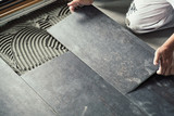 Worker placing ceramic floor tiles on adhesive surface - 209751565