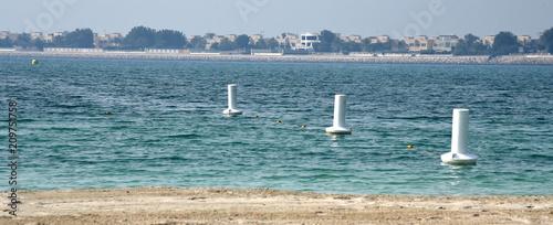 Blick vom Sandstrand auf das türkisblaue Meer mit drei weißen Bojen - 209751758