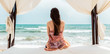 Woman sitting in beach bed looking at the sea, serene scene