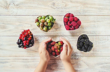 Berries in the hands of a child in the form of a heart. Home. Selective focus.