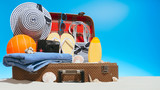 Suitcase with sand and travel supplies