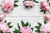 frame made of pink peony flowers over white wooden table with copy space. flower composition. top view. flat lay