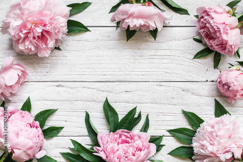 Foto Murales frame made of pink peony flowers over white wooden table with copy space. flower composition. top view. flat lay