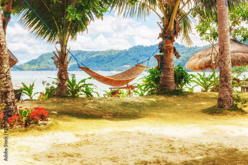 Fotobehang Tropical strand Tropical beach. A hammock between two palm trees on the beach. Concept of rest. Beautiful beach.